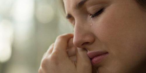 Eine weinende Frau trocknet sich die Tränen.