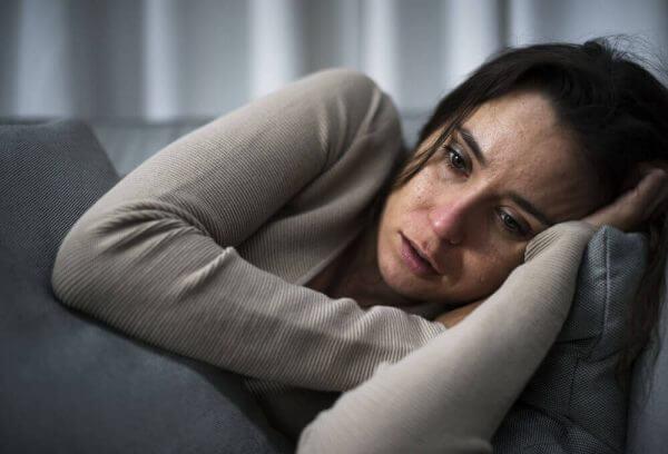 Eine Frau weint auf der Couch.