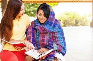 Eine westliche und eine indische Frau lesen zusammen.