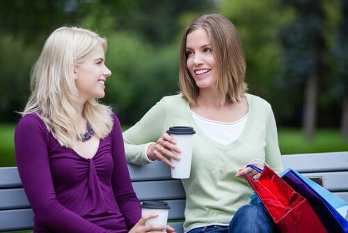 Frauen unterhalten sich auf einer Parkbank.