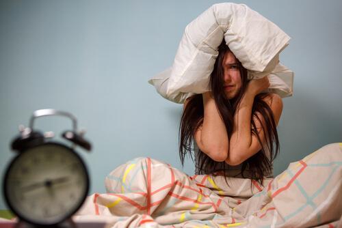 Eine frustrierte Frau zieht sich ein Kissen über den Kopf.