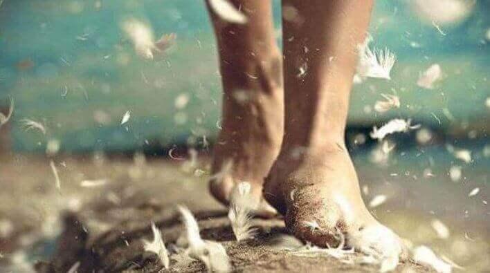 Füße im Sand umgeben von umherfliegenden Federn
