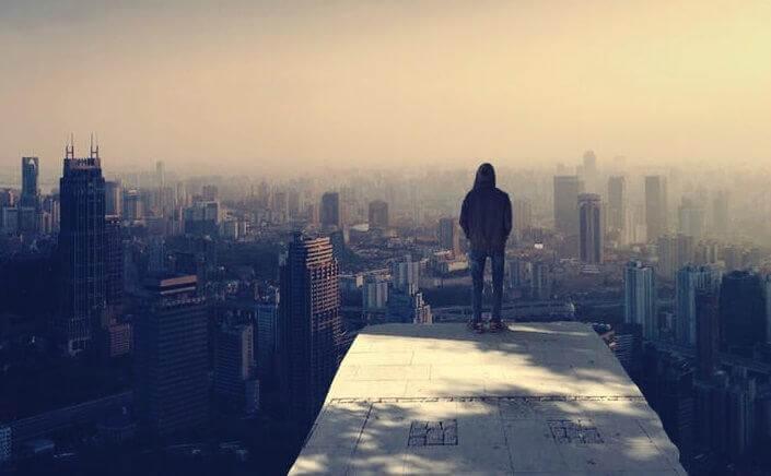 Mann steht auf einem Gebäude und schaut auf eine Stadt hinunter