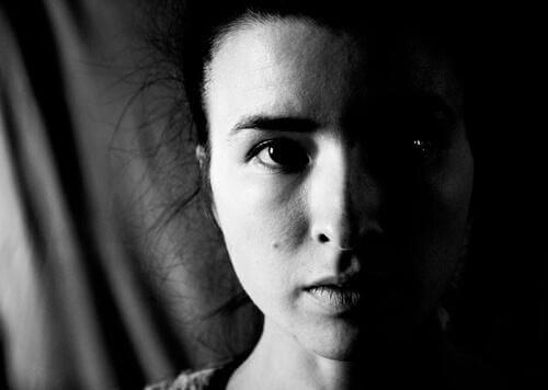 Das ernste Gesicht einer Frau, das halbseitig von einem Schatten verdeckt wird