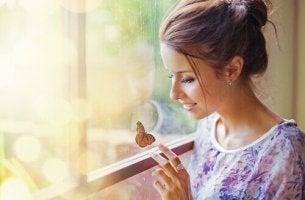 Frau betrachtet glücklich einen Schmetterling.