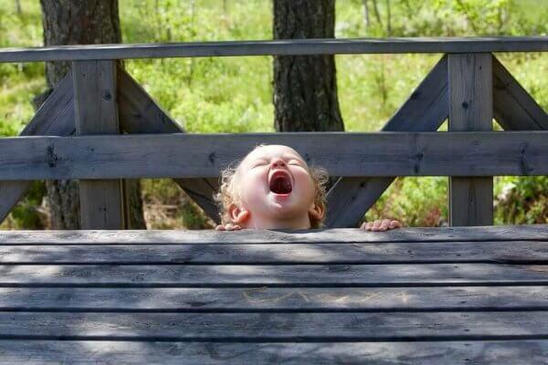 Ein Kleinkind versteckt sich und ruft laut aus.