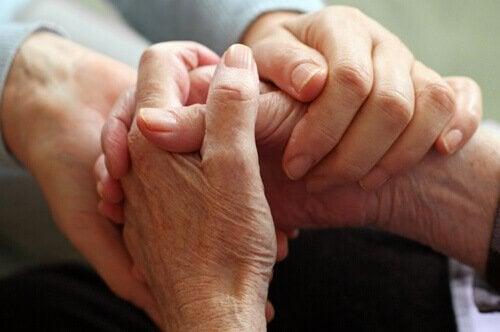 Ein junger Mensch und ein älterer Mensch halten sich an den Händen.