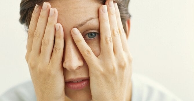 Eine Frau hat ihre Hände vors Gesicht geschlagen.