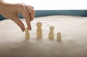 Eine Hand platziert Spielfiguren im Sand.