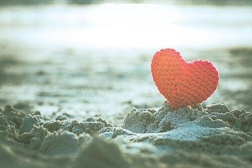 Ein rotes Herz steckt im Sand.