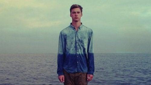 Junge am Meer; das Wasser steht ihm scheinbar bis zum Bauchnabel