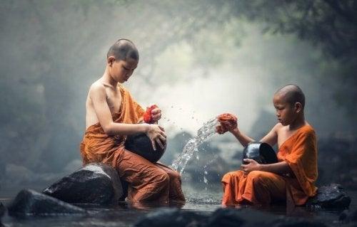 Zwei junge buddhistische Mönche schöpfen Wasser.
