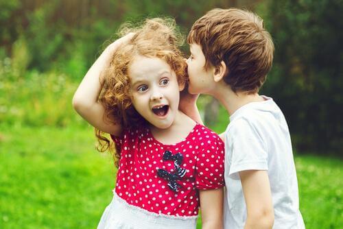 Ein Junge flüstert einem Mädchen etwas ins Ohr