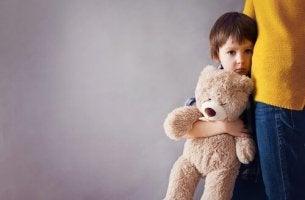 Junge mit Teddy klammert sich an seine Mutter