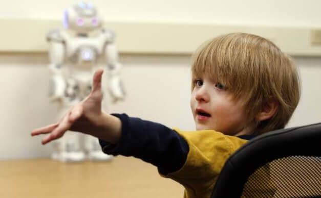 Ein Junge streckt seine Hand aus, im Hintergrund wartet ein Roboter auf seinen Einsatz.