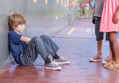 Ein trauriger Junge sitzt auf dem Fußboden und zwei Kinder stehen vor ihm und zeigen mit ihren Fingern auf den Jungen.