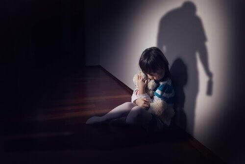 Ein Kind verkriecht sich mit seinem Teddy