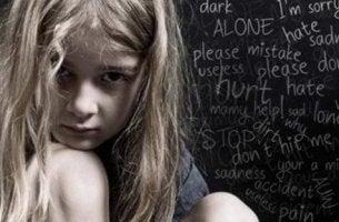 Verbale Misshandlung - Kind sitzt vor einer Tafel mit bösen Worten