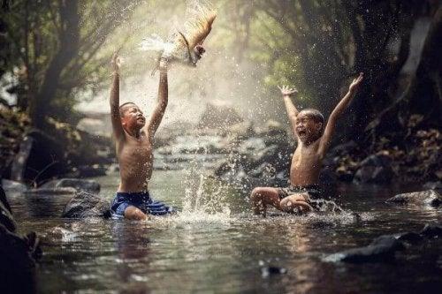 Zwei asiatische Jungen spielen in einem Fluss.