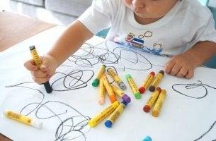 Zeichnung eines Kindes - Junge kritzelt auf ein Blatt Papier