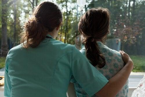 Eine Krankenschwester hat ihren Arm um eine Patientin gelegt.