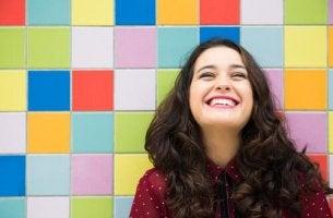 Eine lachende Frau steht vor einer Wand aus bunten Kacheln.
