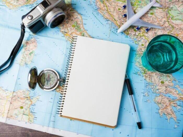 Landkarte mit Notizblock und kleinem Flugzeug