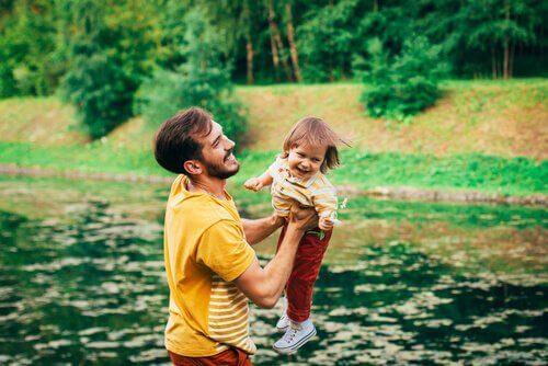 Vater hebt sein lachendes Kind vor einem See hoch