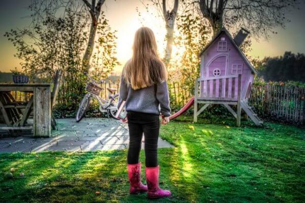 Ein Mädchen steht allein in einem Garten.
