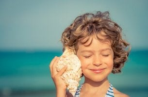 Ein Mädchen hält sich eine Muschel ans Ohr