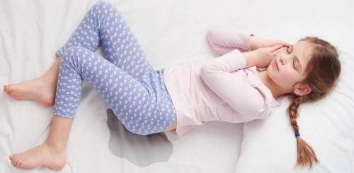 Mädchen liegt eingenässt im Bett.