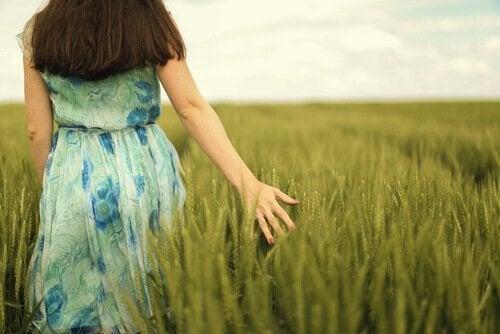 Eine Frau geht durch ein grünes Getreidefeld.