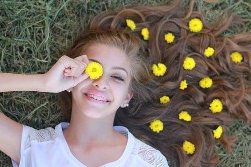 Mädchen hält eine gelbe Blume vor ihr Auge.