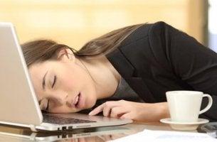 Eine junge Frau ist an ihrem Laptop eingeschlafen.