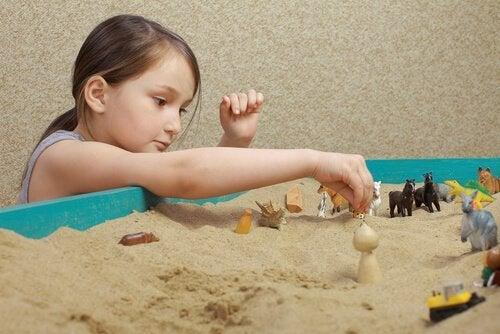 Ein Mädchen spielt in einer Sandkiste.