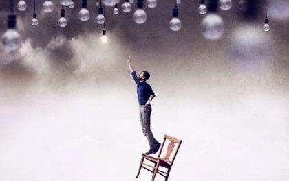 Ein Mann balanciert auf einem Stuhl und versucht, eine Glühbirne zu erreichen.