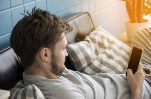 Ein Mann liegt auf dem Sofa und guckt auf sein Handy