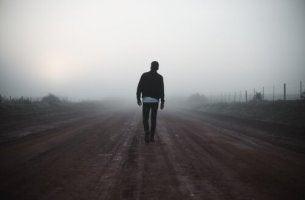 Ein Mann auf einem Weg im Nebel.