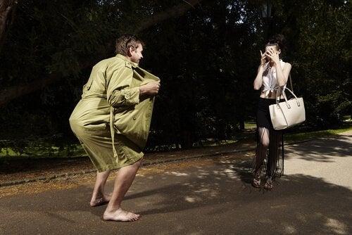 Mann öffnet seinen Mantel vor einer Frau