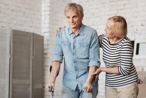 Ein älterer Mann geht auf Krücken und wird dabei von einer Frau gestützt.