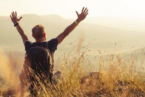 Ein Wanderer auf einem Berg reckt die Arme in Glückspose hoch.