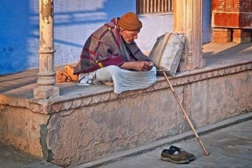 Ein alter Mann in Indien schnitzt.