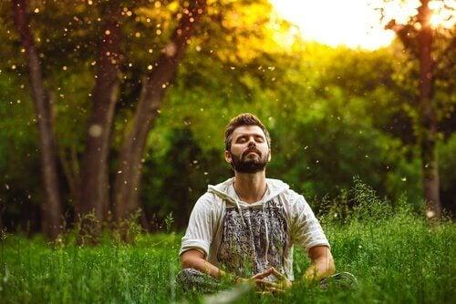 Ein Mann sitzt in einem Feld und meditiert.
