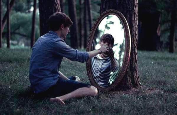 Mann sitzt in einem Wald auf dem Boden und blickt in einen Spiegel
