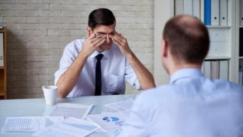 Ein Mann reibt sich im Büro müde die Augen.