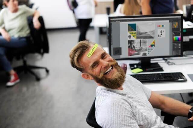 Ein Mann im Büro hat ein Post-it auf der Stirn und lacht.