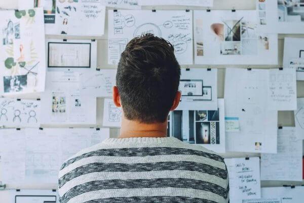 Ein Mann starrt auf eine Sammlung von Notizen an der Wand.