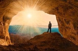 Mann schaut aus einer Höhle auf die aufgehende Sonne.