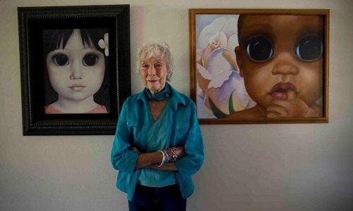 Margaret Keane steht vor ihren Werken.