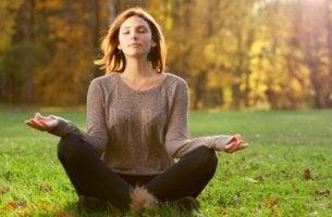 Eine Frau meditiert im Grünen.